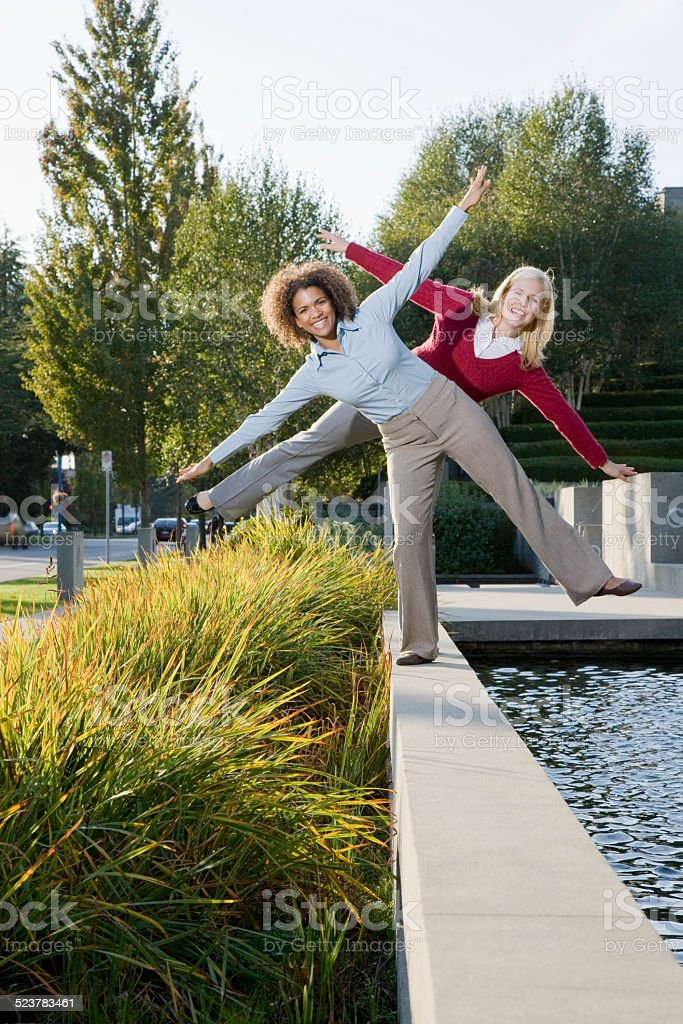 Ladies in suit balancing at fountain side stock photo