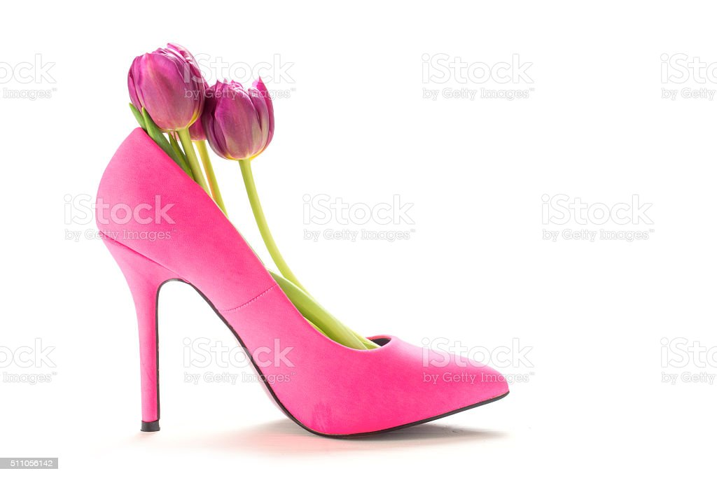 Ladies pink high heel shoe with tulips, isolated on white stock photo