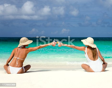two happy women on the beach enjoying a cocktail