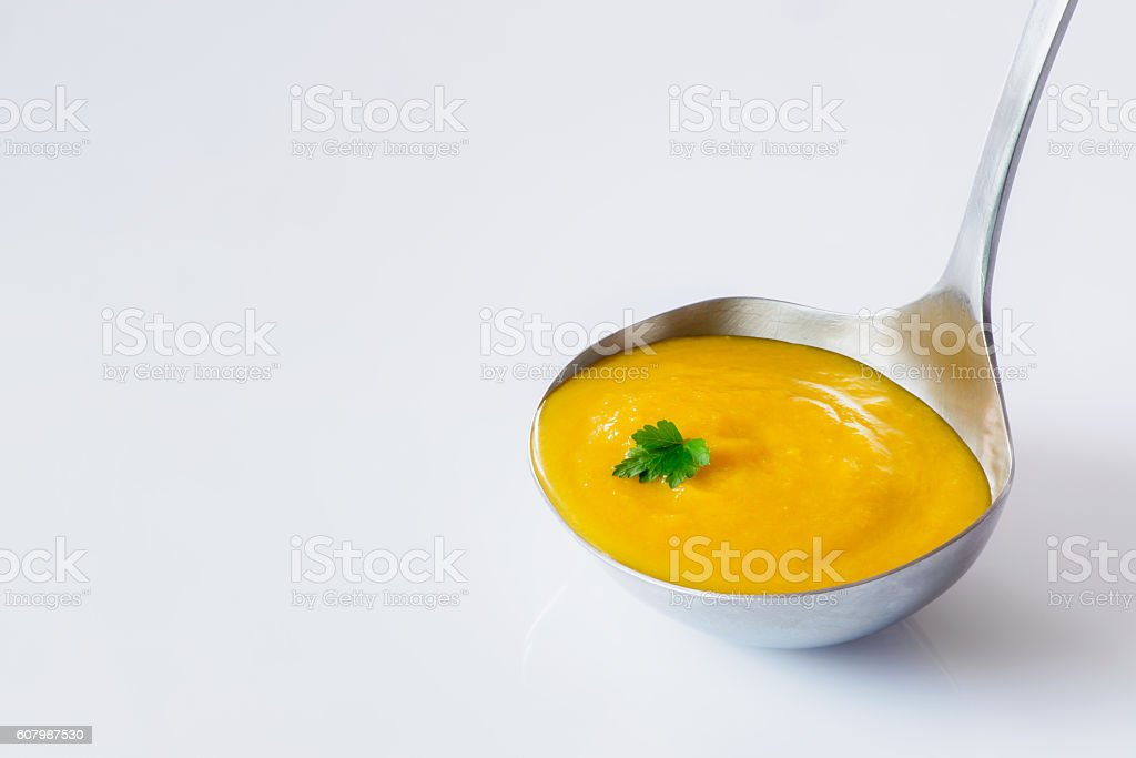 Ladle carrot ginger soup stock photo
