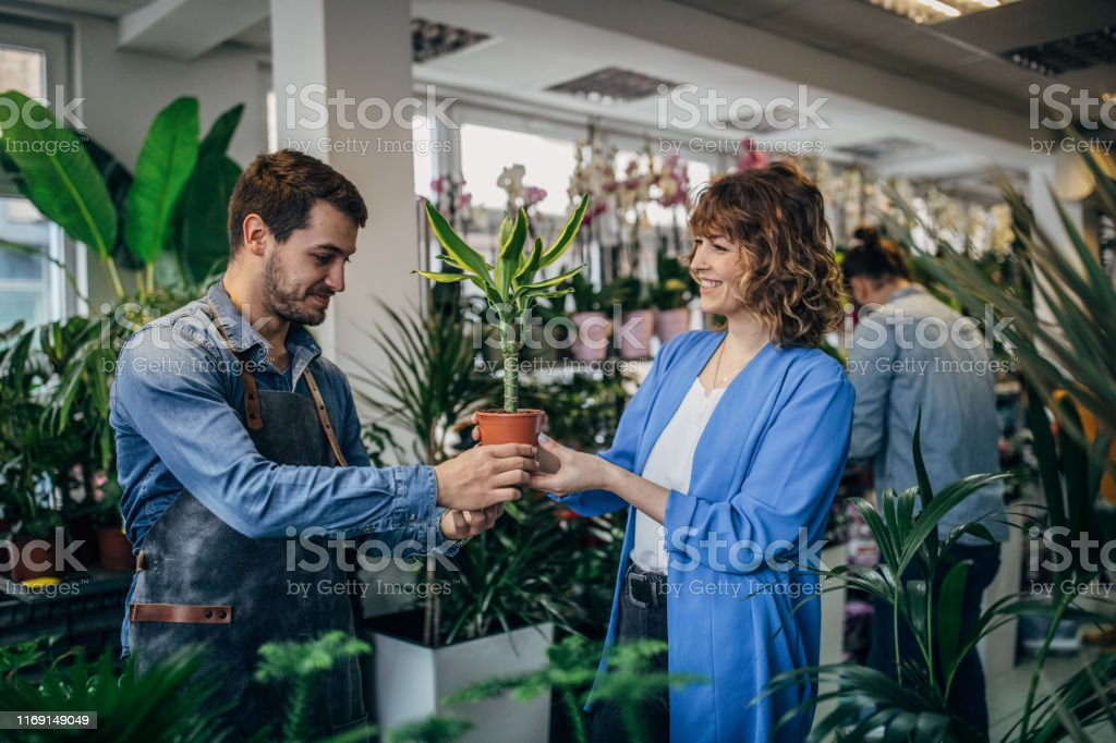 Group of people at the flower shop, woman buying plants of a florist.