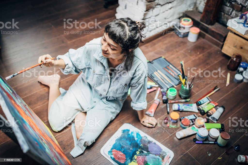 One woman, beautiful lady artist, painting on the floor in studio.