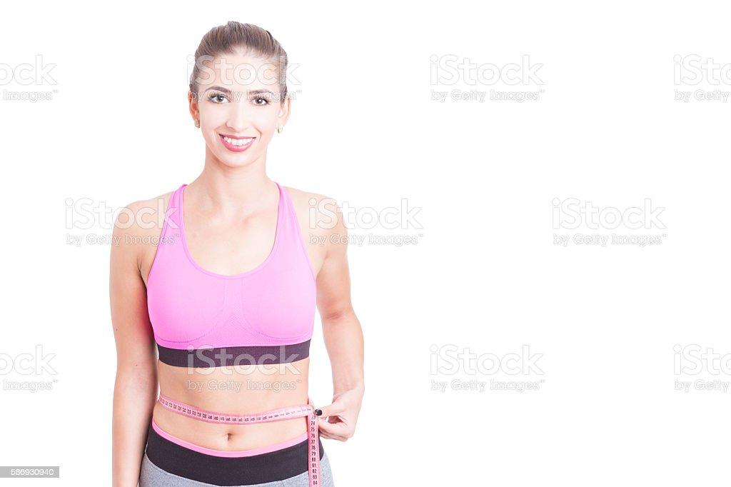 Lady at gym holding tape line around waist stock photo