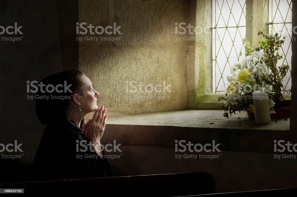 Lady at prayer stock photo