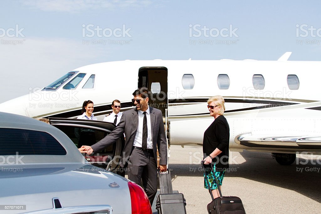 Lady being assisted by chauffeur stock photo