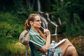 One woman, lady explorer and biologist contemplating in nature by waterfall alone.