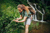 One woman, lady explorer and biologist using magnifying glass in nature by waterfall alone.