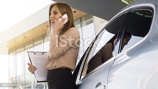 istock Lady broker with contract talking with client on smartphone, standing near car 962477416