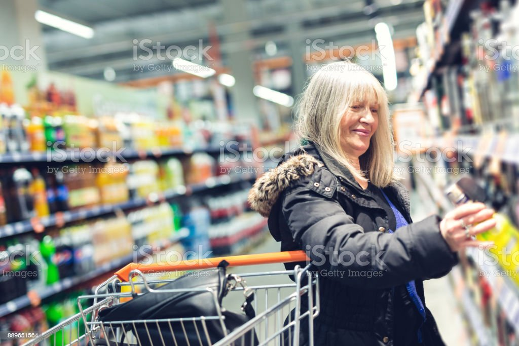 Lady choosing drink in a store stock photo