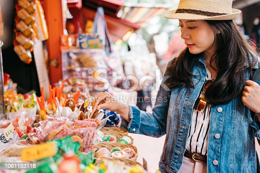 elegant lady choosing sweets at the candy vendor in the traditional market. traveler looking at the specialties in Mexican outdoor vendors. travel in America lifestyle.