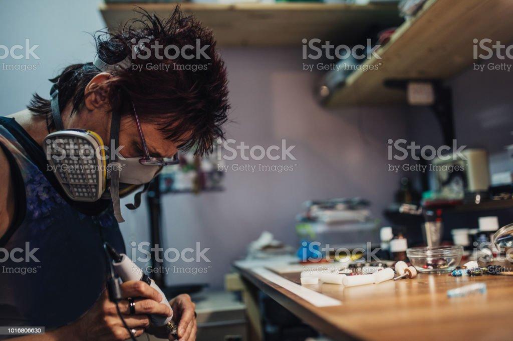 One mature woman, sitting alone in work shop, making handmade jewelry.