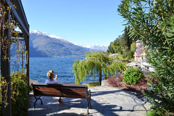 Lady eating an ice-cream sitting on a bench at the lake Como lakefront. stock photo