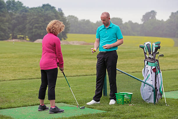 Lady golfer being taught by a golf pro. stock photo