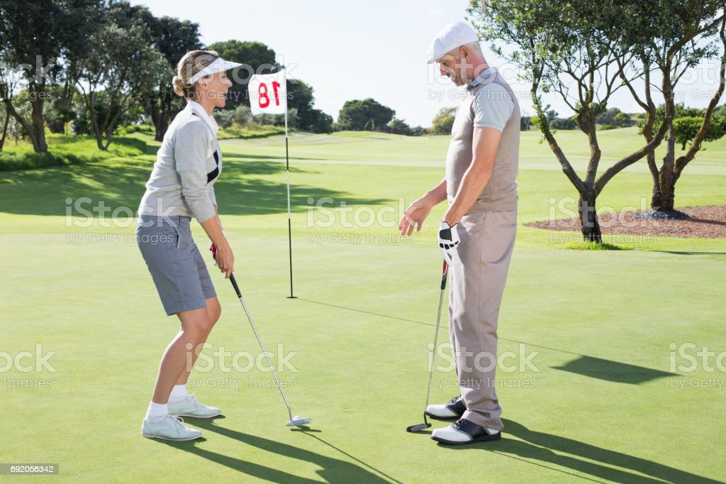 Lady golfer on the putting green at the eighteenth hole with partner stock photo