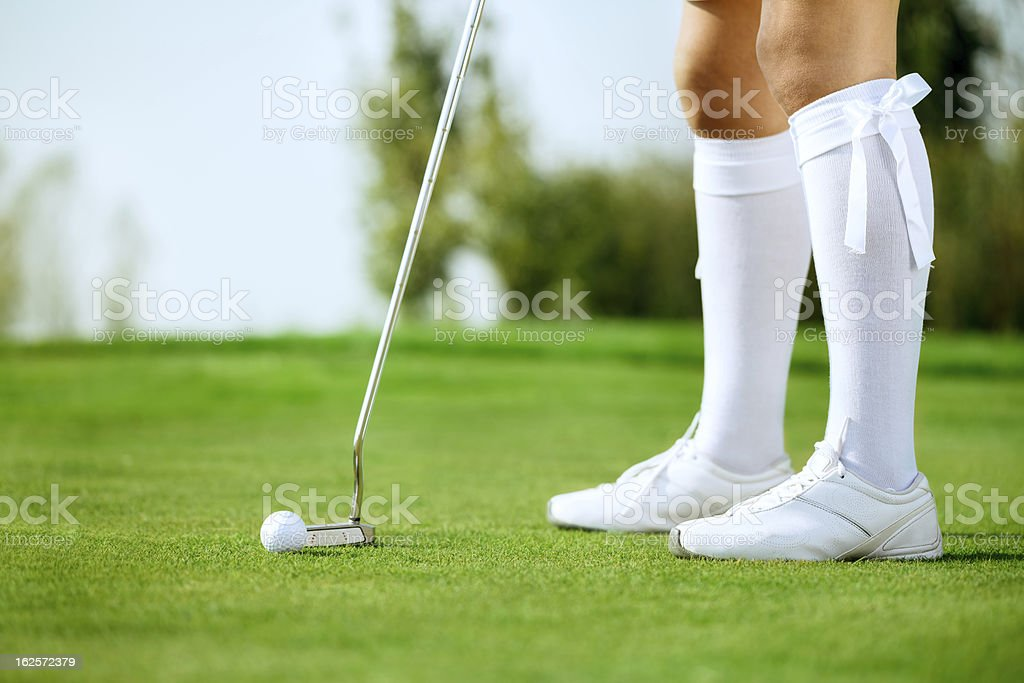 Woman\'s legs, golfing on the green, woman putting ball
