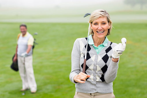 Lady golfer smiling at camera with partner behind