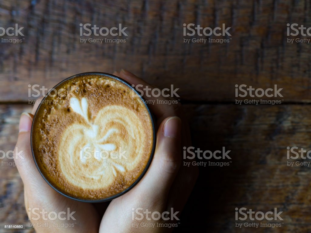 Lady hands holding latte art coffee cup on brown wooden table background, morning time stock photo