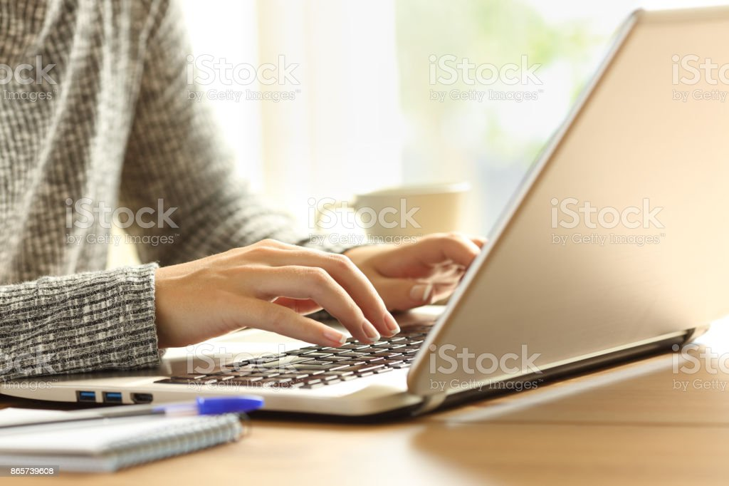 Lady hands typing in a laptop on a desk stock photo