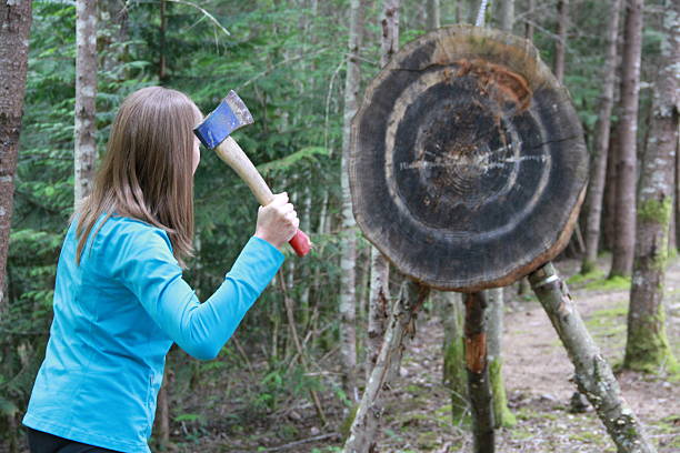 Lady Hatchet Thrower A young woman is preparing to throw a hatchet at a large target in the forest. throwing stock pictures, royalty-free photos & images
