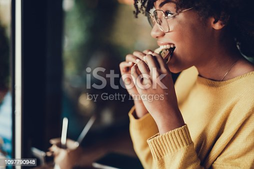 Cropped portrait of beautiful young woman. She eating frest sandwich for breakfast in cafe