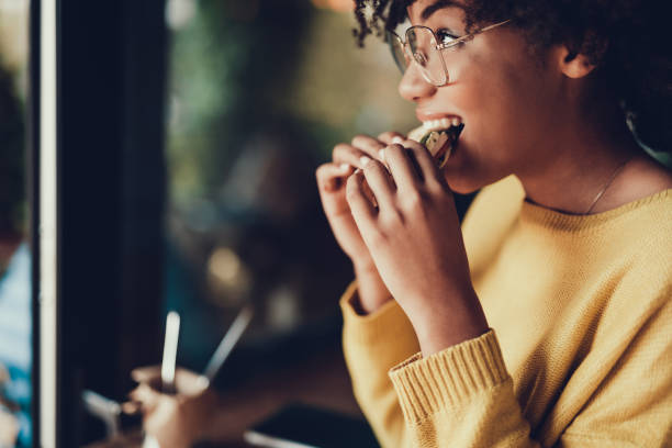 Lady having dinner in small family restaurant Cropped portrait of beautiful young woman. She eating frest sandwich for breakfast in cafe eating stock pictures, royalty-free photos & images