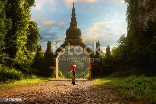 Lady hold red umbrellas with arch at Khao Na Nai Luang Dharma Park in Surat Thani Thailand