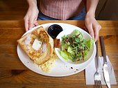A lady holding plate with toast and fresh salad.