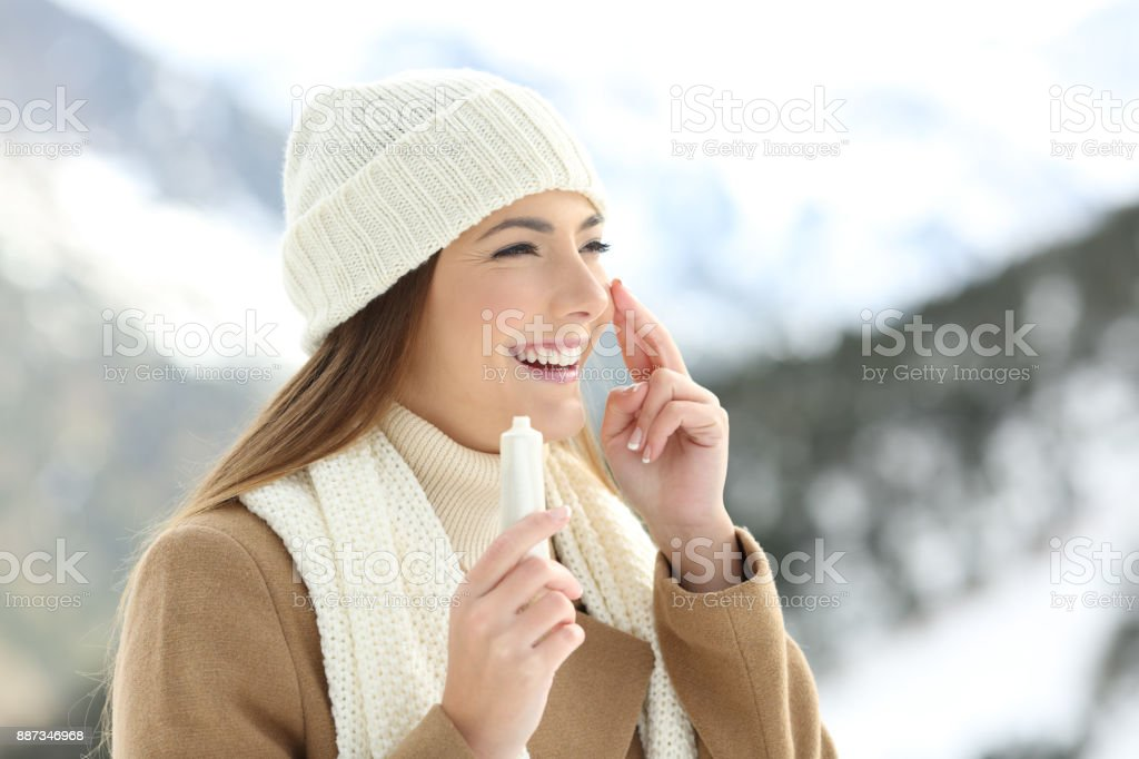 Lady hydrating face skin with moisturizer cream stock photo