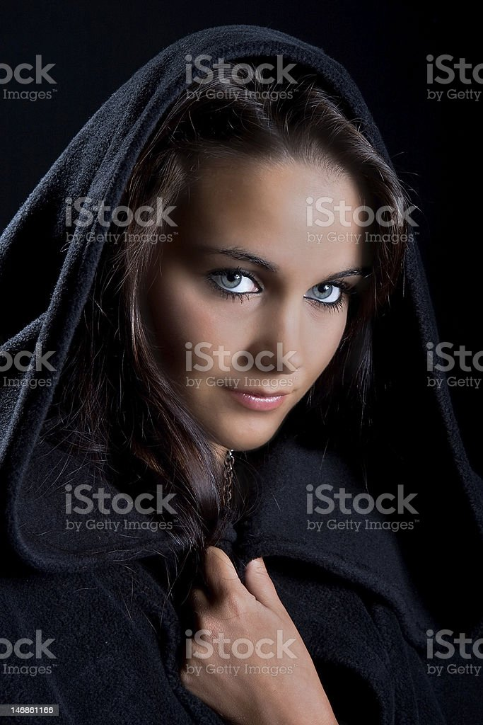 Lady in a black cape Dramatic portrait of a young lady in a black cape, may-be a young witch Adult Stock Photo
