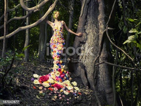 istock Lady in a dress of flowers posing in a wood 157042877