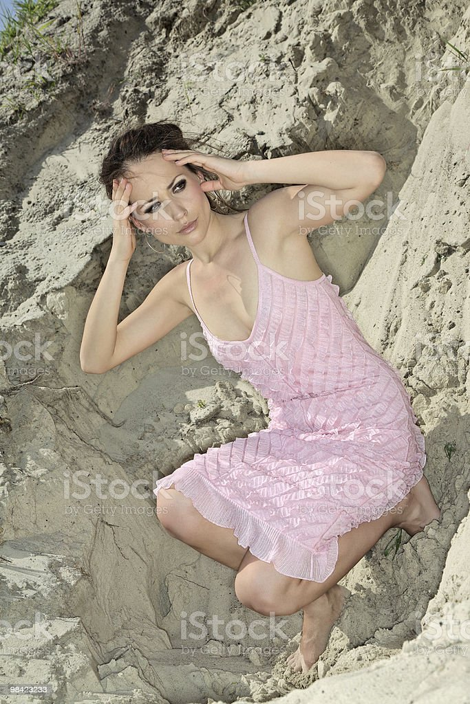 Lady in a pink scaly sundress on sand quarry royalty-free stock photo