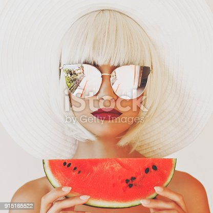 istock Lady in hat and sunglasses with watermelon 915165522