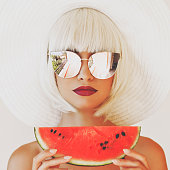 Lady in hat and sunglasses with watermelon