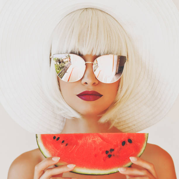 Lady in hat and sunglasses with watermelon stock photo