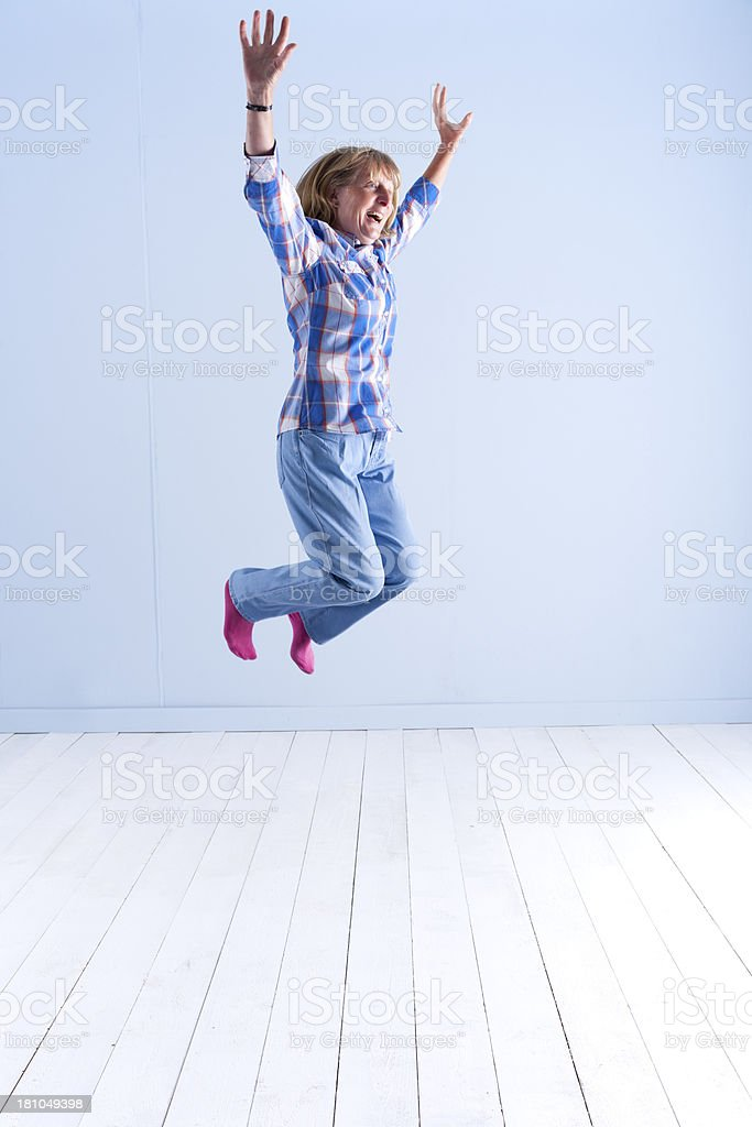 Lady In  Her 60s Jumping For Joy royalty-free stock photo