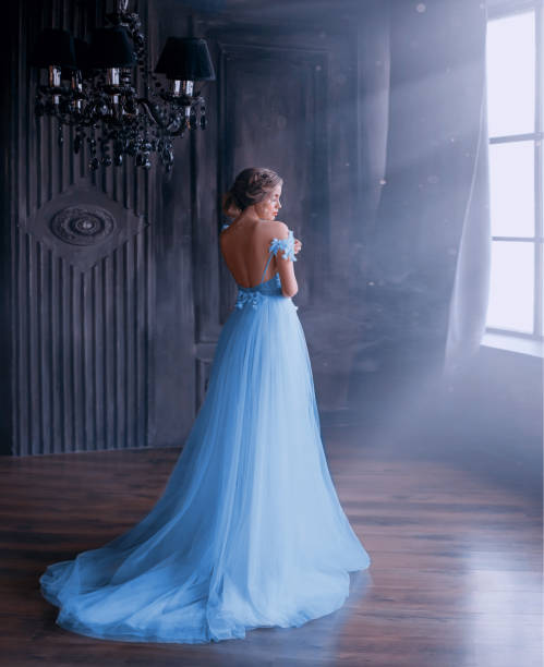 lady in long blue vintage dress with train and open back stands with back to camera. room with large windows with sunlight. Happy woman at a luxury party. Gothic interior, huge black chandelier. lady in long blue vintage dress with train and open back stands with back to camera. room with large windows with sunlight. Happy woman at a luxury party. Gothic interior, huge black chandelier sun shining through dresses stock pictures, royalty-free photos & images