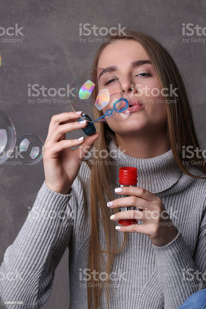 Lady in pullover blowing bubbles. Close up. Gray background royalty-free stock photo