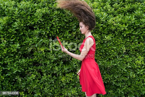 538883870istockphoto Lady in red amazed by something on her tablet 957344336
