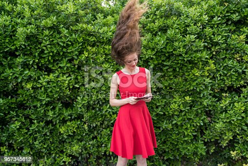 538883870istockphoto Lady in red dress amazed by something on her tablet 957345612