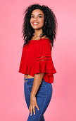 istock Lady in red. Gorgeous Afro-American woman in a red blouse and blue jeans is posing in semi-profile with her head turned to the camera and smiling broadly. 1182101153