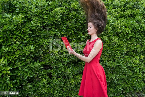 538883870istockphoto Lady in red thrilled by something on her tablet 957344464