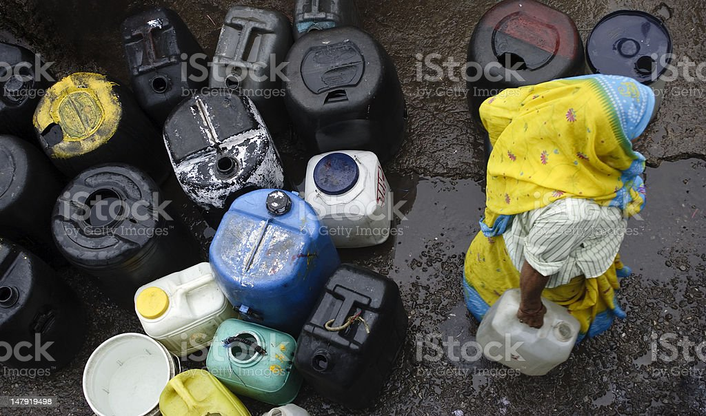 Lady in sari with gallon for storage of water stock photo