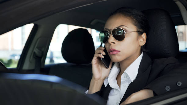 lady in sunglasses sitting in car and talking on cellphone, police agent on duty - female spy stock photos and pictures