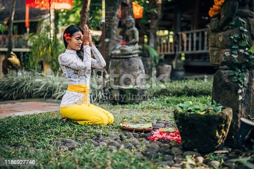 One woman, young lady in traditional Balinese clothing praying outdoors.