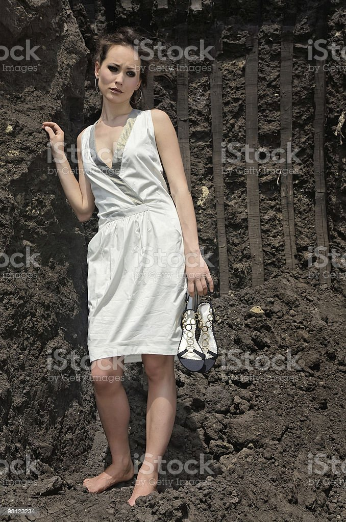 Lady in white sundress inside a deep black ground quarry royalty-free stock photo