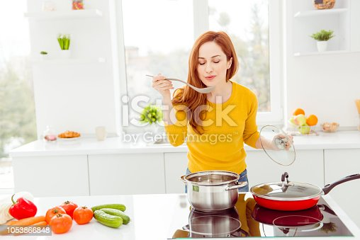 Lady in yellow pullover, with tomato, cucumber, pepper, cabbage, carrots on the table in modern white bright cozy, comfort interior make yummy dish for breakfast for family