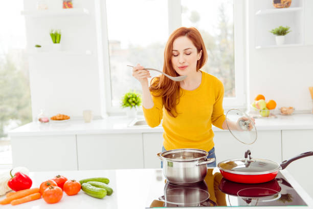 lady in yellow pullover, with tomato, cucumber, pepper, cabbage, carrots on the table in modern white bright cozy, comfort interior make yummy dish for breakfast for family - assaggiare foto e immagini stock