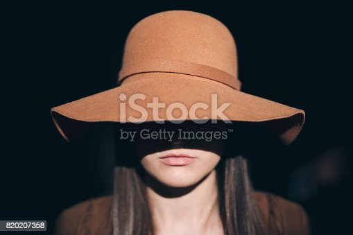 Unrecognizable young woman posing in the dark, hiding her face behind floppy hat.