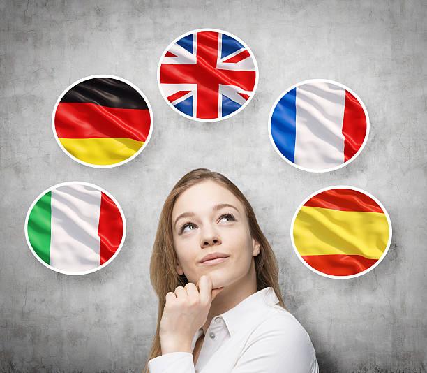 lady ist umgeben von blasen mit europäischen länderflaggen - spanisch translator stock-fotos und bilder