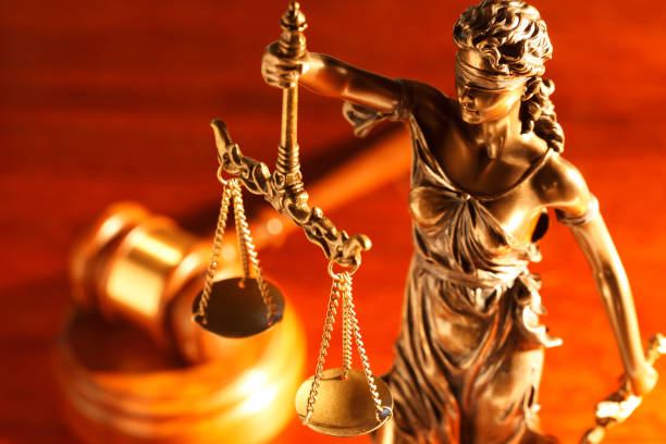 Lady Justice And Gavel On Desk A gavel rests out of focus in the background behind a statue of lady justice.  The image is photographed with a veryshallow depth of field. lawsuit stock pictures, royalty-free photos & images